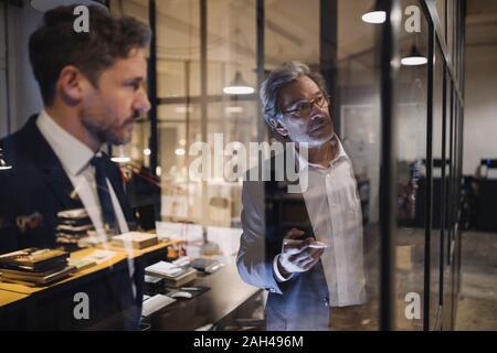 Deux hommes d'affaires travaillant sur le dessin sur vitre in office