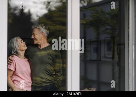 Happy senior couple derrière la vitre de leur accueil Banque D'Images