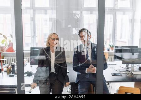 Businessman and businesswoman looking at dessin sur vitre in office