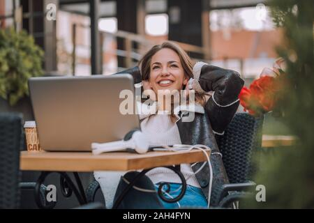 Jeune femme assise au café de la rue Main dans la main derrière sa tête et souriant pendant l'utilisation d'ordinateur portable.