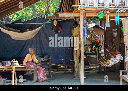 Femme âgée balance le berceau de bébé, à Bagan, Myanmar Banque D'Images