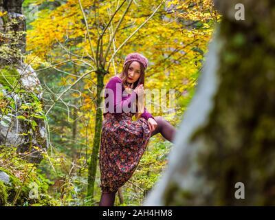Campagne-fille countrygirl dans la campagne isolé sérieusement regarder caméra eyeshot yeux-contact mettre une jambe sur la posture de l'arbre pose poser posant une tristesse triste Banque D'Images