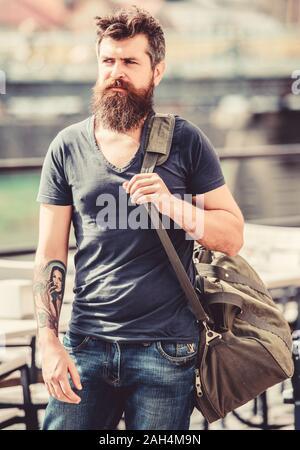 Voyages et vacances concept. L'homme musclé avec barbe et moustache exerçant son gros sac de sport. Explorer Tourisme Ville avec assurance. Support de sac sur son épaule. Faire les choses en grand sac sur l'épaule. Banque D'Images