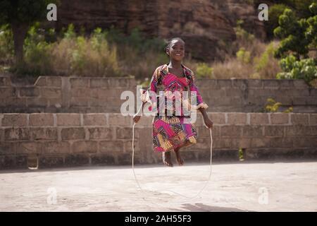 Souriante Jeune fille africaine se réchauffer avec une corde à sauter dans l'arrière-cour