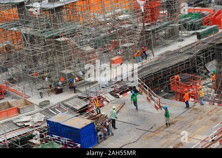 Bangkok, Thaïlande - le 23 décembre 2019 Gros plan: cadre d'acier soit proposé par grue a tour tandis que deux travailleurs la marche et le tenant at construction site Banque D'Images