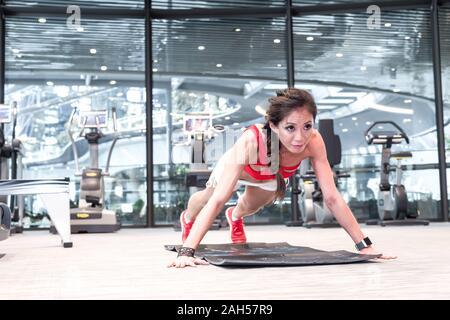 Une femme d'origine asiatique fit active en position push-up Banque D'Images