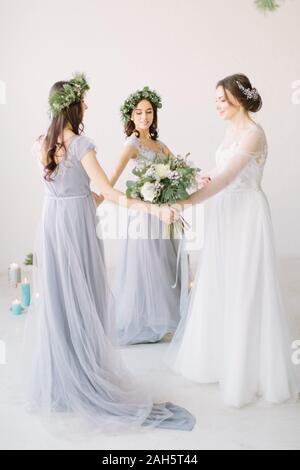 Mariée et demoiselles se tenant la main et la danse de white studio. Portrait pleine longueur. Banque D'Images