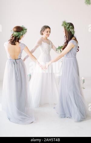 Jolie mariée et demoiselles se tenant la main et la danse de white studio. Portrait pleine longueur. Banque D'Images