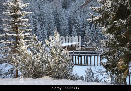Les arbres couverts de neige la petite maison en bois du châssis suspendu sur le lac gelé Banque D'Images