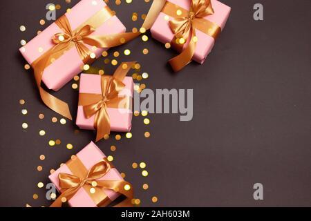 Joyeux Noël et de bonnes vacances carte de vœux cadeau doré sur fond sombre, vue du dessus. Mise à plat d'une composition pour anniversaire, mère, jour joyeux c