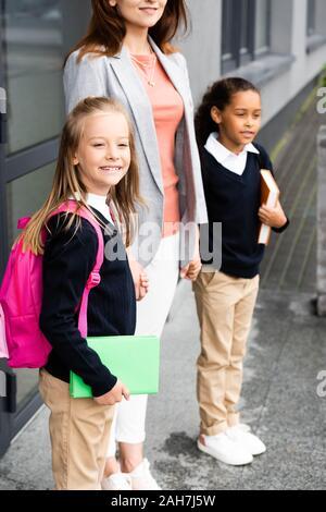 Portrait de mère tenant les mains de deux filles en uniforme de l'école multiculturelle