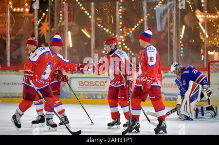 Le président russe Vladimir Poutine, #11, est félicité après avoir marqué lors d'un match de hockey sur glace dans la ligue de hockey de nuit à la patinoire du grand magasin GUM sur la Place Rouge le 25 décembre 2019 à Moscou, Russie.