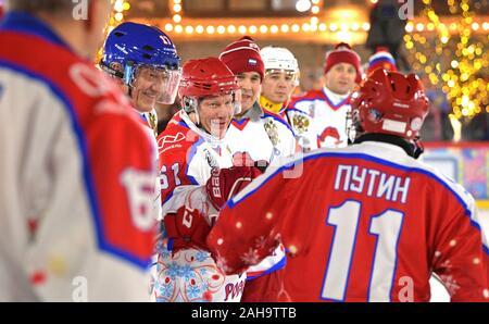 Le président russe Vladimir Poutine, #11, accueille les joueurs pendant un match de hockey sur glace dans la ligue de hockey de nuit à la patinoire du grand magasin GUM sur la Place Rouge le 25 décembre 2019 à Moscou, Russie.