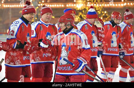 Le président russe Vladimir Poutine, #11, salue des coéquipiers pendant un match de hockey sur glace dans la ligue de hockey de nuit à la patinoire du grand magasin GUM sur la Place Rouge le 25 décembre 2019 à Moscou, Russie.