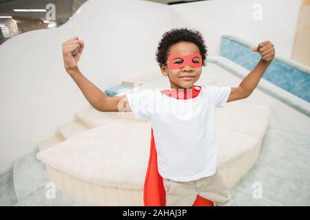 Petit garçon mignon solide d'origine ethnique africaine porter du rouge manteau de super héros