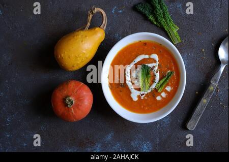 Vue de dessus de soupe au potiron avec de la crème d'épices sur fond sombre. Banque D'Images