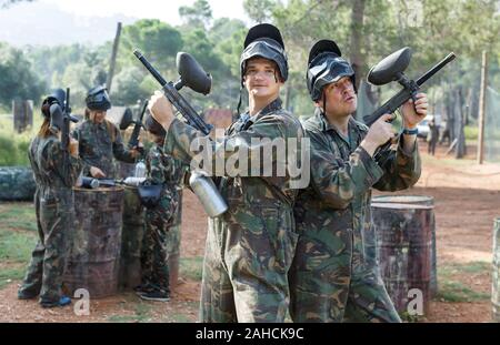 Deux hommes en tenue de camouflage avec des armes prêtes pour le paintball en plein air avec des amis Banque D'Images