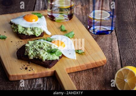 Petit-déjeuner ou un brunch le jour de la Saint-Valentin, avocat toasts de pain de seigle avec œuf frit servi sur planche de bois rustique, repas végétarien sain pour deux personnes Banque D'Images