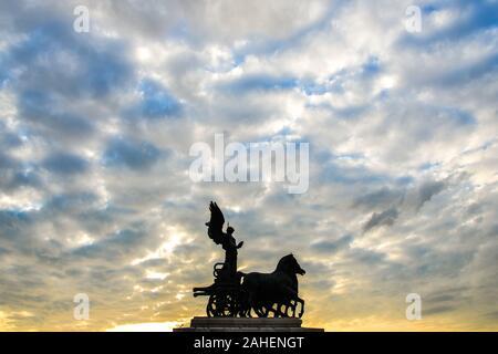 Statue de la Déesse Victoria équitation sur Quadriga sur le haut du monument de Vittorio Emanuele II au coucher du soleil à Rome, Italie. Banque D'Images