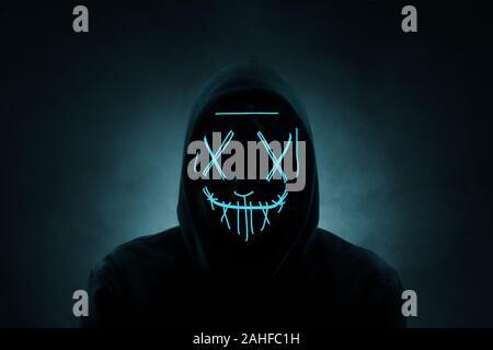 Portrait d'un homme anonyme, hacker portant masque sur fond sombre au néon