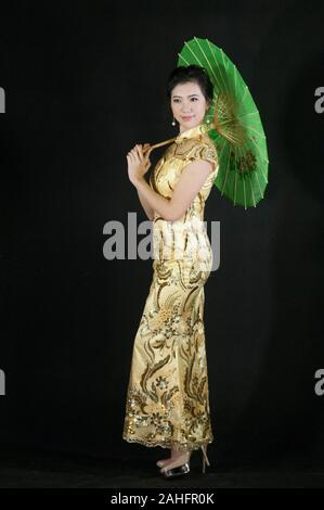 Portrait de femme d'origine asiatique, en permanent pose détendue de vêtements traditionnels chinois qipao cheongsam ou un style traditionnel et holding green parasol Banque D'Images