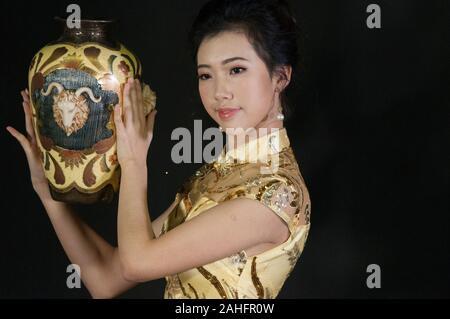 Tête et épaules de femme d'origine asiatique, vêtu du costume traditionnel chinois qipao cheongsam ou un style traditionnel Banque D'Images
