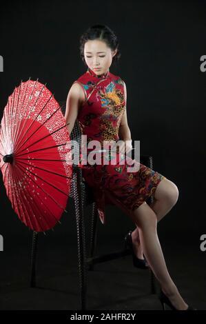 Femme d'origine asiatique, dans diverses poses wearing traditional Chinese cheongsam qipao ou un style traditionnel Banque D'Images