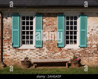 De simples volets bleus autour des fenêtres blanches contre un mur de brique dans maison coloniale en Virginie Banque D'Images