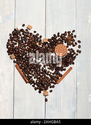 Coeur fait d'aliments et d'épices sur fond de bois vintage. Motif de grains de café, biscuit, morceaux de sucre, d'anis et de cannelle. Symbole de l'amour est l'acronyme de sweet feeling. L'amour et de l'alimentation concept art Banque D'Images