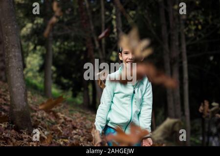 Petite fille souriante regardant des feuilles brunes voler dans la forêt. Gamin ludique avec veste polaire verte s'amuser dans les bois le jour de l'automne Banque D'Images
