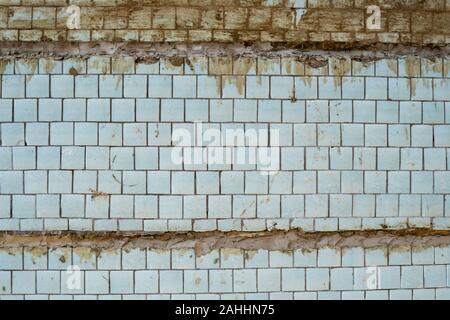 Carreaux bleus sur un mur comme une image d'arrière-plan. Vieux Bleu carreaux avec des joints entre dalles de béton. Banque D'Images