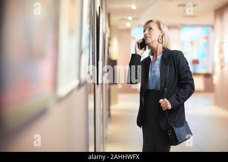 Portrait de femme mature élégante en parlant tout en profitant de l'exposition smartphone galerie d'art ou un musée, copy space