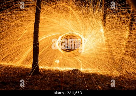 Cercle de feu de la filature de la laine d'acier la création d'étincelles en spirale, filage de la laine d'acier cercle de feu de la filature de la laine d'acier la création d'étincelles en spirale, bouleau grov Banque D'Images
