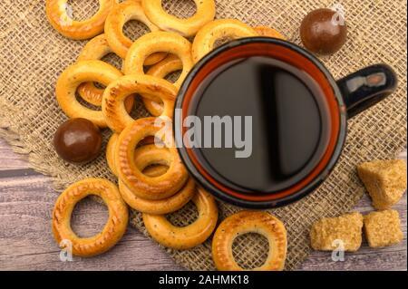 Bagels, petits chocolats, une tasse de thé et un tissu de fabrication locale sur un fond de bois close-up Banque D'Images