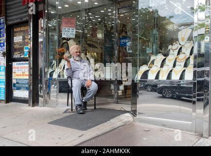 Sur une chaude journée d'automne, un joaillier Sikh se trouve à l'extérieur son magasin seul dans ses pensées. Sur 74e Rue à Jackson Heights, Queens, New York. Banque D'Images