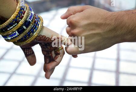 Libre de droit d'une main d'homme et woman's hands holding petits doigts de l'autre isolated over white wall background. Banque D'Images