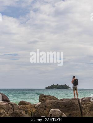 Un backpacker est la randonnée le long de la côte, temps nuageux, l'océan et les rochers Banque D'Images