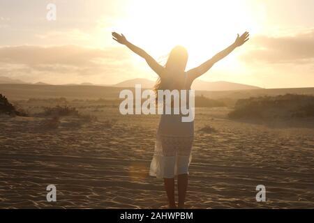 Coucher du soleil dans le désert. Jeune femme avec avec bras levés wearing white dress balade dans les dunes du désert sable pendant le coucher du soleil. Fille sur le sable doré sur cor