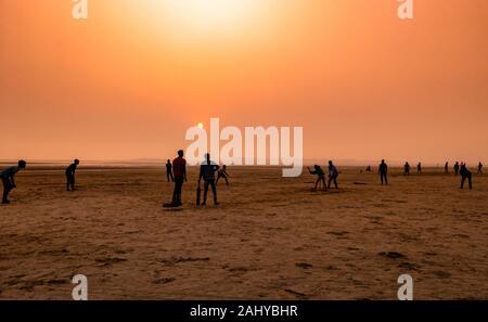 Silhouette de personnes , jouer au cricket au moment de coucher de soleil sur une plage.