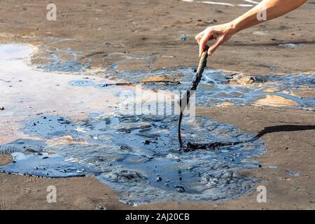 A woman's hand asphalte liquide en remuant avec un bâton en bois à la hauteur tonale, le lac le plus grand dépôt de bitume dans le monde. La Brea, Trinité-islan