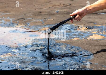 La main d'un homme d'asphalte liquide en remuant avec un bâton en bois à la hauteur tonale, le lac le plus grand dépôt de bitume dans le monde. La Brea, Trinidad, île