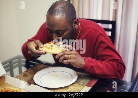 L'homme afro-américain de manger une tranche de pizza à la maison