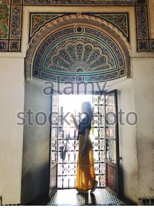Femme en robe bleue debout sur la fenêtre Banque D'Images