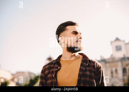 Portrait d'un jeune homme hippster confiant contre un ciel dégagé en ville Banque D'Images