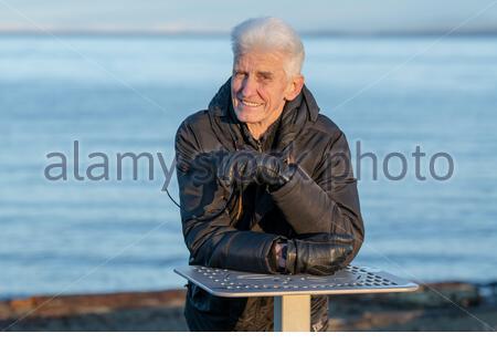 Une attractive senior man smiling comme il se penche sur une table en métal sur la plage. Mis en valeur par les eaux de l'océan bleu de Parksville beach dans l'arrière-plan. Banque D'Images