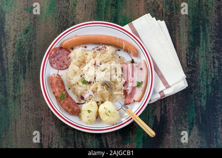 Choucroute garnie, une plaque alsacienne typique, avec des saucisses, du bacon, de la choucroute et des pommes sur fond de bois Banque D'Images