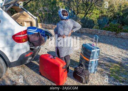 Mode de vie et de voyage concept: femme dos valises de chargement dans la voiture Banque D'Images