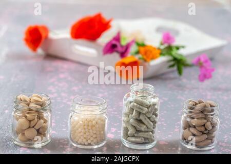 Suppléments de fines herbes et vitamines sur plateau en bois , décoré de fleurs et d'herbes médicinales colorées floues à fond de bois Banque D'Images