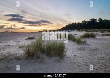 Lever du soleil sur les huttes de plage et les dunes de sable de Wells à côté de la plage de la mer, Wells-Next-the-Sea, Norfolk, Angleterre, Royaume-Uni, Europe