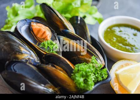 Moules cuites avec des herbes et citron plaque sombre contexte / des fruits de mer les fruits de mer sur le bol et sauce épicée au restaurant alimentaire shell de moules